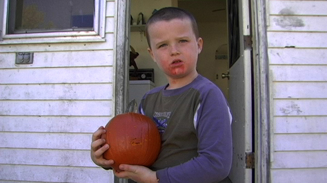 A young boy shows off his Halloween jack-o-lantern.