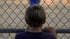 A young boy watches his friends' baseball game through the fence.