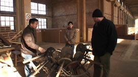 Ai Weiwei and his craftsmen look at one of his furniture works in his workshop on the outskirts of Beijing, in the Zuoyou Art Studio complex.