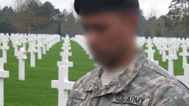 A soldier pays his respects at the American cemetery in Normandy, France