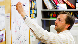 Dr. Ben Kilminister (particle physics researcher) at his whiteboard