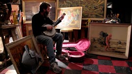 Wayne White playing the banjo in his studio