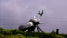 A giant silver kabuto mushi by the side of a highway