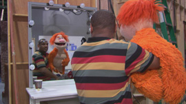 "Kevin Clash on the set of The Game with the puppet ""Mookie"" in Being Elmo"
