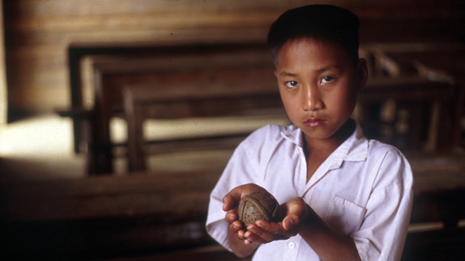 A Lao student holds a clay bombie, made as part of a bombie-awareness lesson