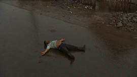 A man sleeps on a street in Carmens village