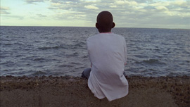 Main character Denick staring out at the sea on the main boulevard of Cap-Haitien