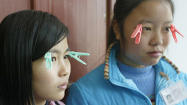 To avoid getting fined for falling asleep, Jasmine (17) and Li Ping (14) use clothespins to keep their eyes open.