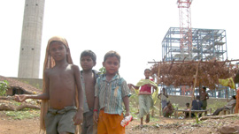 Tribal land is taken over by a British mining company as tribal children face camera.