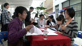 Wan Chao presents his CV at a job fair.