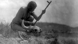 Black and white photo of Plains Indian with bison skull and prayer pipe