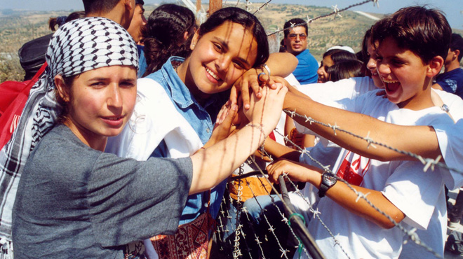 Samar and Miriam hold hands with children from the Dheisha camp at the Lebanese-Israeli border, South Lebanon