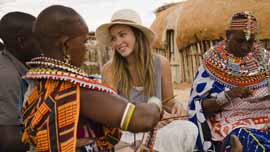 Olivia Wilde learns how to make beaded jewelery with women from Umoja Women's Village in Samburu, Kenya.