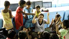 America Ferrera plays with children at the New Light Crche in Kolkata, India.