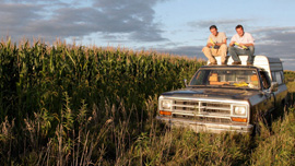 Ian Cheney and Curt Ellis rest on top of a pickup truck