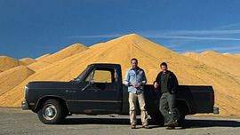 Ian Cheney and Curt Ellis in front of a pile of surplus corn
