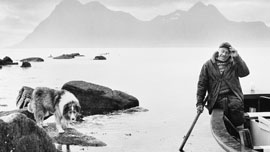 Fisherman Axel with eyes closed waiting for his flask of coffee, and his dog Tyri standing on a skerry