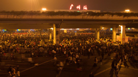 Guangzhou Railway Station illuminated in the dark with stranded passengers impatiently waiting for trains to go home.