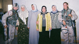 Specialist Shannon Morgan posing with Iraqi women in Ramadi, Iraq, 2004