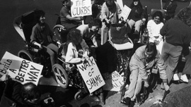 Protesters break a curb in the mid-1980s