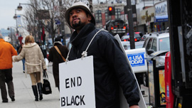 Director Shukree Tilghman wears a protest sign in Harlem
