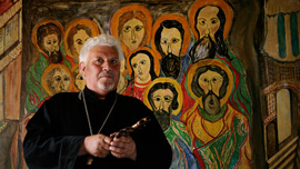 "Father Dimitar, priest at the Belene prison's chapel ""St Nikolay Mirlikiiski"" in front of the chapel's iconostasis."