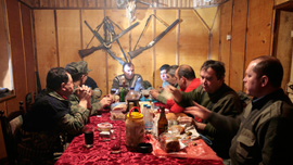 Hunters chatting around a well-laden table