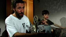 Borya and Mark watching home movies of Borya's childhood during the 1970s in the USSR