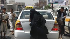 A woman walks by Abu Jandal's taxi.