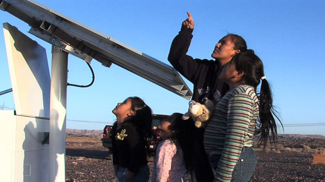 Melissa Yazzie and her children get a solar panel installed