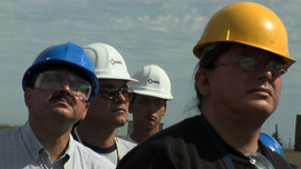 Native workers view the construction of a wind turbine