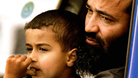 Abu Amar al Azzam waiting with his son Abu Bakr al Azzam in their van