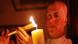 Father Paul O'Brien, Parish Priest at Saint Patrick Parish, Lawrence, MA, lights candle at Easter Vigil