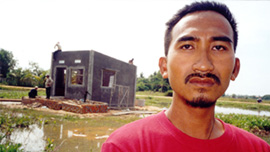 Loeun Lun in front of his new home in Siem Reap, Cambodia