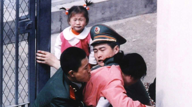 Two-year-old Han-mi looks on in agony as her mother is wrestled to the ground by Chinese guards