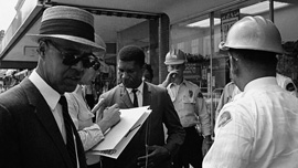 Medgar Evers surrounded by police