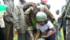 Maathai helps a young girl water the land in the Aberdare Forest, Kenya