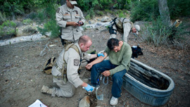 Border Patrol agents help an ailing migrant crosser