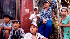 Street kids in Vietnam who wander Ho Chi Minh City selling postcards, trinkets and lottery tickets