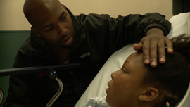 Demia Bruce comforts his daughter Deja Bruce in The Waiting Room