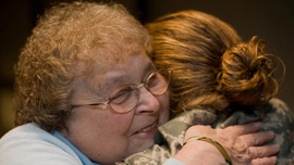 Joan Gaudet gives a hug to a returning soldier