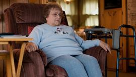 Joan Gaudet sits in her living room