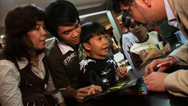 Naif Al-Mutawa signing a comic for a young fan in Jakarta