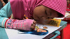 Indonesian girl coloring in a sketch of Noora The Light 