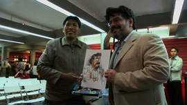 Naif Al-Mutawa holding a comic rendering of himself illustrated by a fan in Jakarta