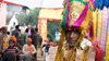 Hari poses wearing his wedding turban with guests in the background.