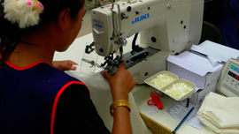 Worker sewing buttons onto a shirt at New Island Clothing factory, Phnom Penh, Cambodia, 2008