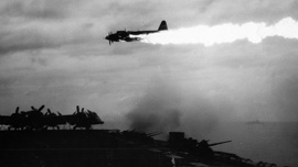 Japanese plane ablaze over escort carrier