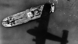 A Coronado bomber casts a shadow over a bamboo-laden Japanese boat in the water in the Western Pacific
