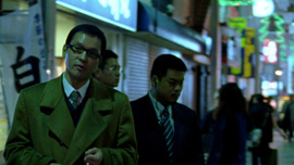 Kumagai-san and two yakuzas walk in the evening in the Tokyo's streets.
